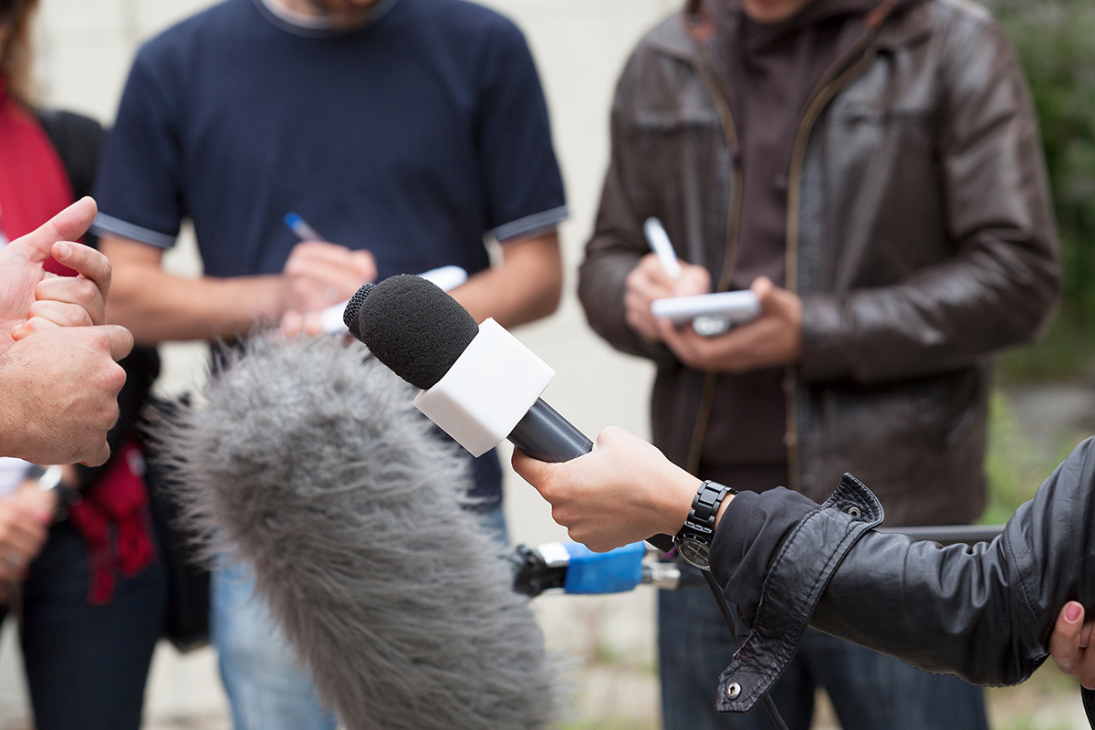 Image of reporters holding microphones