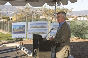 Image of man at podium at groundbreaking of construction project